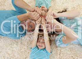 Happy family on floor with heads and hands together