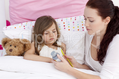 Mother giving her daughter cough medicine
