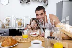 Daughter eating cereals and fruit in kitchen