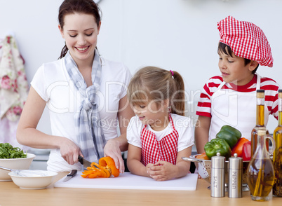 Mother and children cutting vegetables in kitchen
