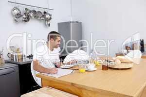 Man working in kitchen while having breakfast