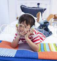 Boy relaxing in bed listening to music