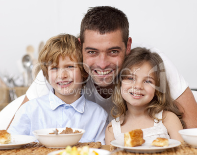 Children having breakfast with their father
