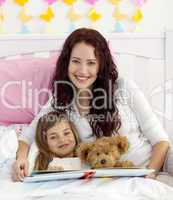 Smiling mother and daughter reading in bed