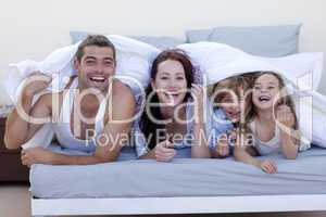 Young family playing in bed together
