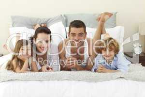 Family lying in bed with pyjamas