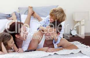 Happy young family having fun in bed