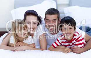 Smiling family lying in bed together