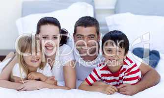 Portrait of family lying in bed together