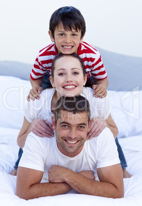 Happy parents and son playing in bed
