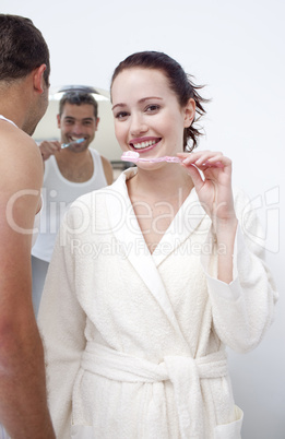Woman and man cleaning their teeth in bathroom