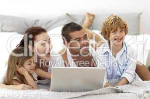 Happy family in bed using a laptop