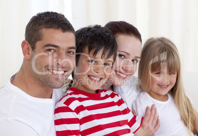 Portrait of parents, daughter and son sitting on sofa together