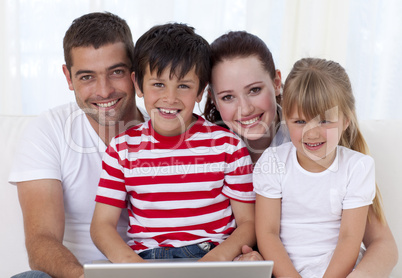 Smiling family at home using a laptop