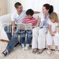 Smiling family in living-room using a laptop