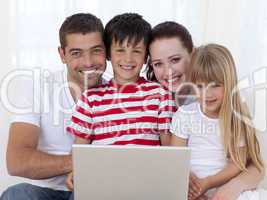 Portrait of family at home using a laptop