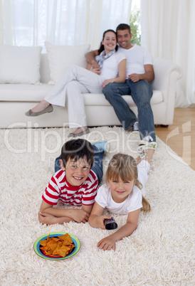 Happy children watching television on floor in living-room