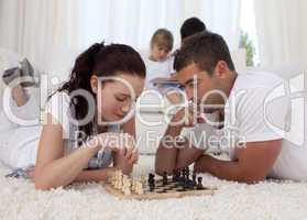 Parents playing chess on floor in living-room