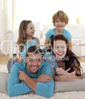 Parents, daughter and son on floor in living-room