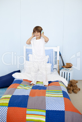 Little boy listening to music and dancing in bedroom