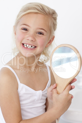 Little girl playing holding a mirror