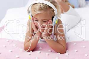 Little girl in bed listening to the music