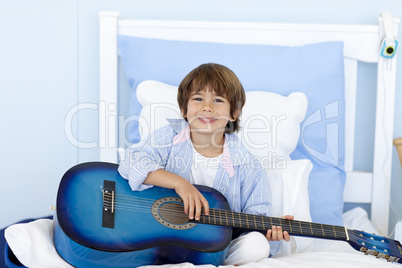 Happy little boy playing guitar in bed