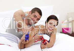 Husband and wife playing videogames in bed
