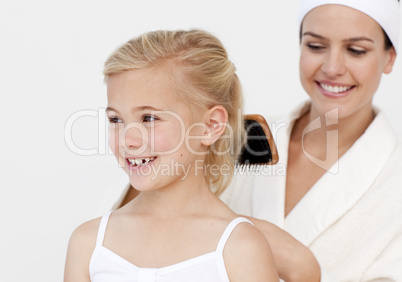 Young mother doing daughter's hair