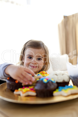 Smiling little girl eating confectionery at home