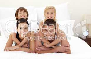 Family having fun in parent's bed