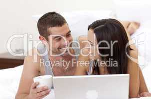 Husband and wife in bed using a laptop