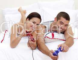 Couple playing videogames in bed