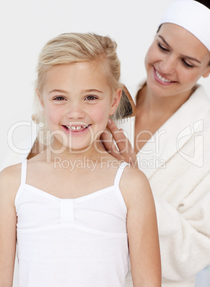 Smiling mother doing daughter's hair