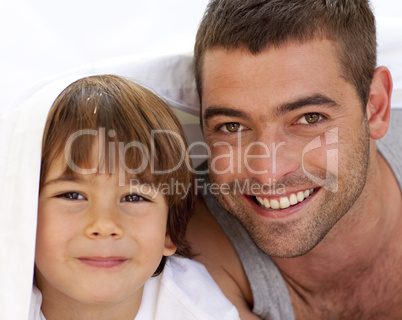 Portrait of dad and son under the bedsheets