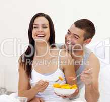 Smiling couple having nutritive breakfast in bed