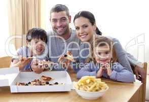 Parents and children eating pizza and fries at home