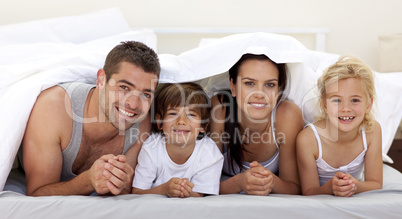 Family playing in parent's bed