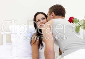 Man holding a rose giving a kiss to his beautiful wife