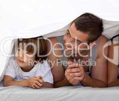 Smiling father and son under the bedsheets
