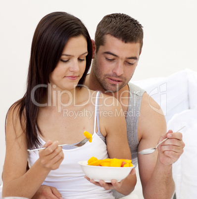 Young couple eating fruit in bed
