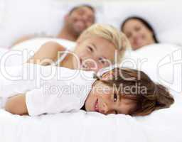 Family resting in parent's bed