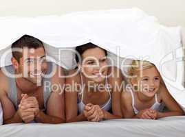 Parents and daughter under the sheets