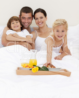 Parents and children having breakfast in bedroom