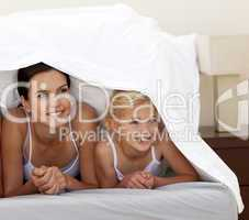 Mother and daughter under the sheets