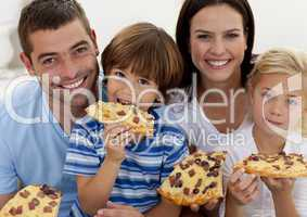 Portrait of family eating pizza in living-room