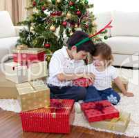 Happy brother and sister opening Christmas gifts
