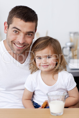 Smiling dad and little girl eating biscuits with milk