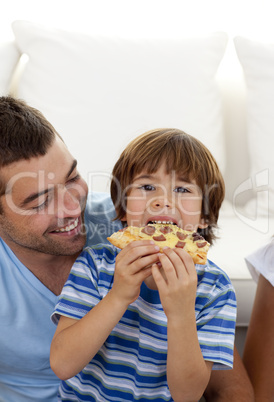Boy eating pizza in living-room with his father