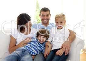 Playful family sitting on sofa at home